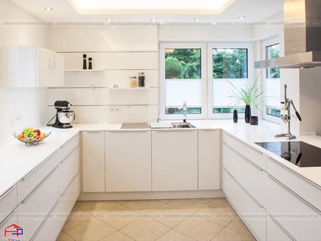 Không gian phòng bếp có diện tích vừa phải được tận dụng tối đa diện tích với mẫu tủ bếp dưới chữ U và kệ trang trí thay thế cho tủ bếp trên