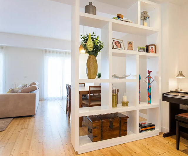 Thiết kế vách ngăn phòng khách và bếp thành tủ trang trí giúp gia đình bài trí những đồ vật yêu thích, thể hiện được nét cá tính riêng biệt