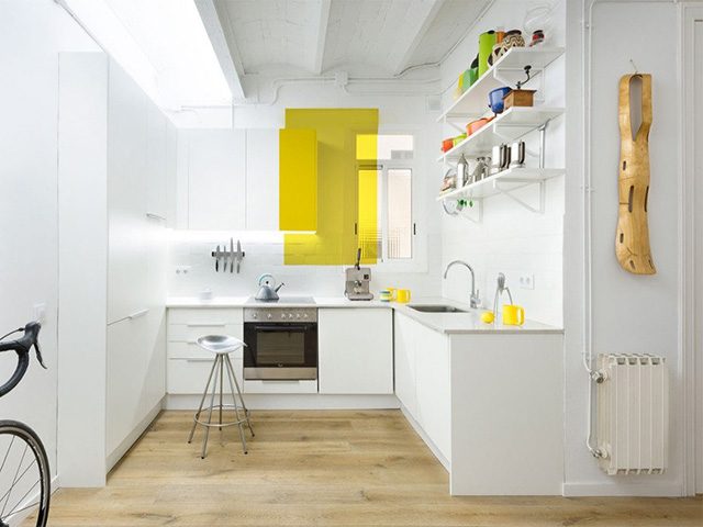 Không gian bếp màu trắng tinh tế được tô điểm thêm bởi màu vàng trẻ trung và ấn tượng