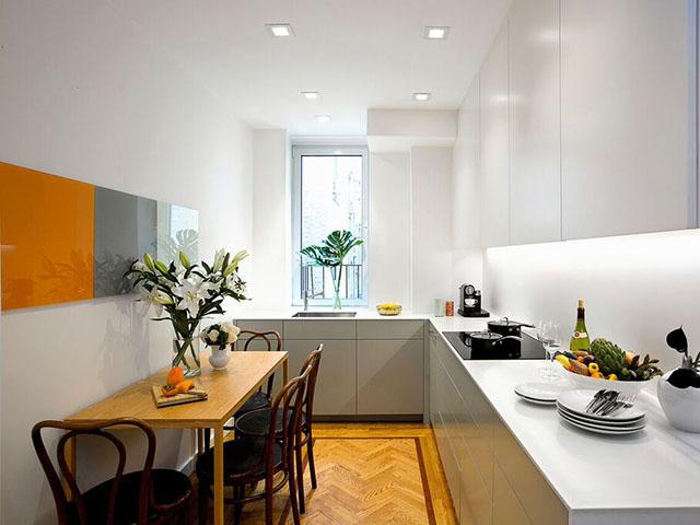 Phòng bếp chung cư có diện tích nhỏ hẹp được tận dụng tối đa không gian với tủ bếp chữ L màu trắng nhẹ nhàng và bộ bàn ăn màu gỗ sang trọng