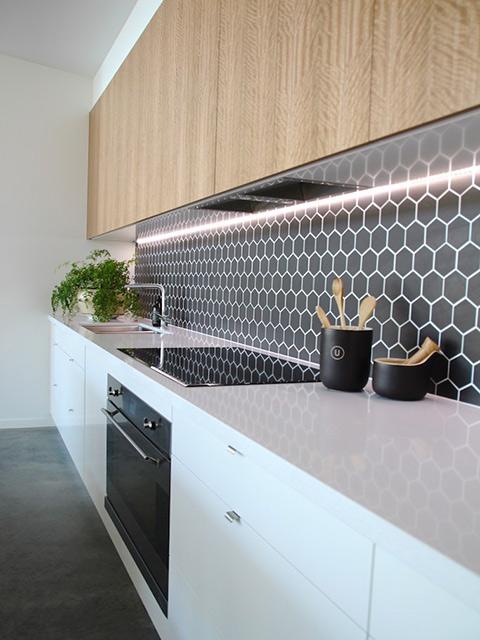 Phòng bếp đẹp hiện đại với tủ bếp chất liệu gỗ công nghiệp màu trắng kết hợp vân gỗ cùng gạch men ốp tường bếp màu đen với họa tiết cực kì lạ mắt