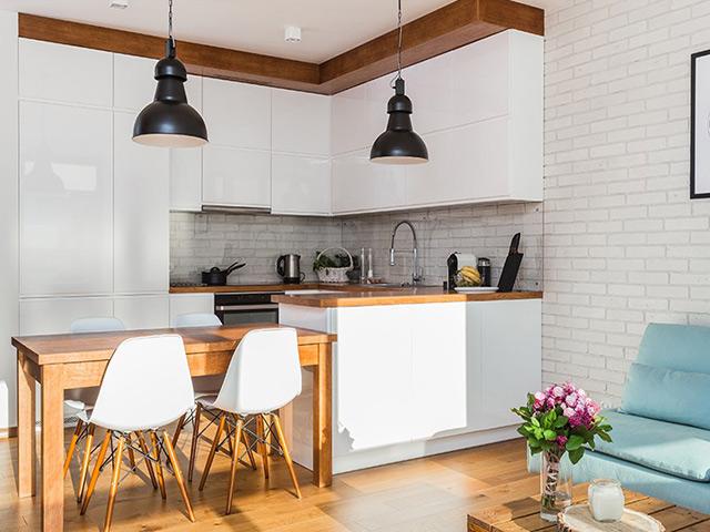 """Mẫu phòng bếp đẹp hiện đại dành cho nhà nhỏ được bố trí liên thông với phòng khách. Một cạnh tủ bếp và bàn ăn chính là """"vách ngăn"""" tạo sự riêng biệt cho 2 không gian"""