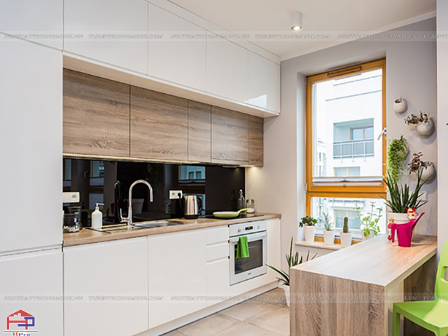 Không gian nhà bếp 12m2 dù nhỏ hẹp nhưng với bộ tủ bếp chữ I kịch trần và bàn ăn nhỏ gọn được bố trí đối diện tạo cảm giác thông thoáng, rộng rãi trong căn phòng