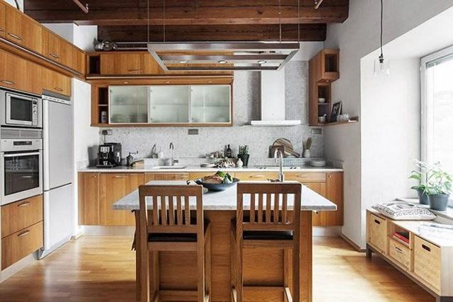 Chất liệu gỗ tự nhiên với gam màu nâu trầm sang tọng tạo nên một không gian nhà bếp ấm cúng. Trần bếp được thiết kế kiểu trần gỗ cực kì mát mẻ