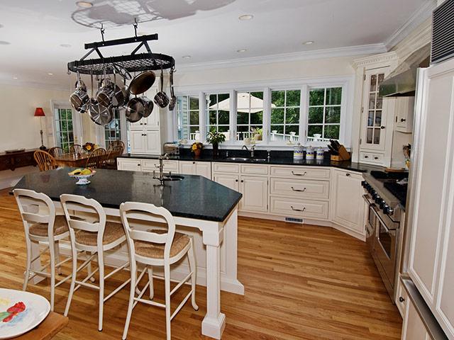 Nhà bếp phong cách đồng quê Anh mang nét đặc trưng từ màu sắc trắng tinh tế, những chi tiết cổ điển từ mặt cánh tủ cho đến đèn trang trí mang đến một không gian đẹp sang trọng