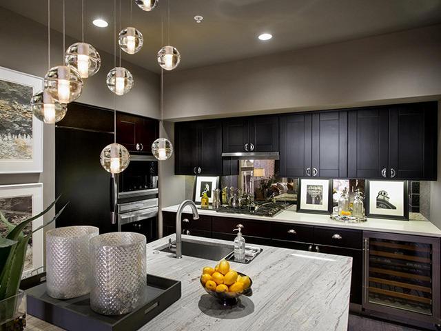 Nhà bếp phong cách đồng quê sử dụng gam màu trầm sang trọng và cực kì sạch sẽ. Những chiếc đèn trần thả tự do mang đến một không gian lãng mạn và ấm cúng